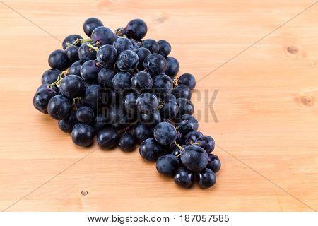 Bunch Of Dark Ripe Grapes On An Oak Natural Wood Table