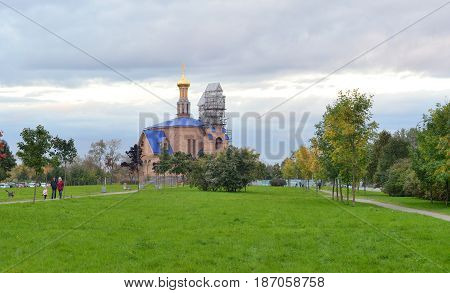 Park in Rybatskoe and church at cloud day in St.Petersburg Russia.
