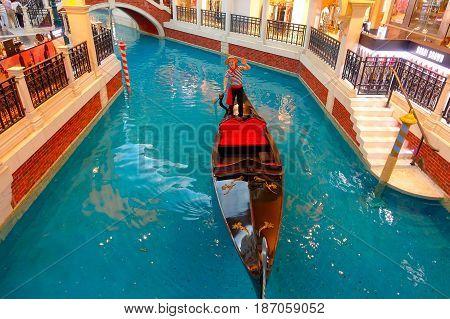 MACAU, CHINA- MAY 11, 2017: An unidentified man having a trip in a venetian gondola inside of a beautiful luxury hotel the Venetian Resort Hotel and Casino.