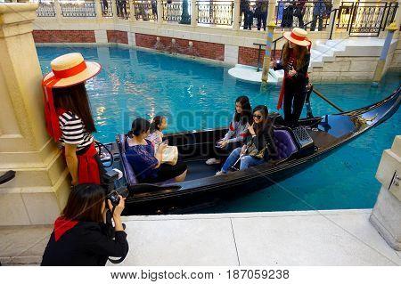 MACAU, CHINA- MAY 11, 2017: An unidentified people having a trip in a venetian gondola inside of a beautiful luxury hotel the Venetian Resort Hotel and Casino.