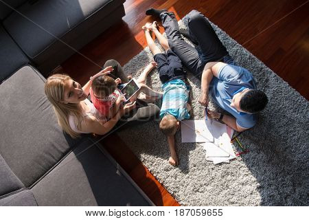Happy Young Family Playing Together at home on the floor using a tablet and a children's drawing set top view