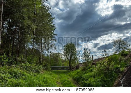 Dramatic Clouds Over A Meadow With A Small Fence Gate And A Path With A Wood Forest Just Beside