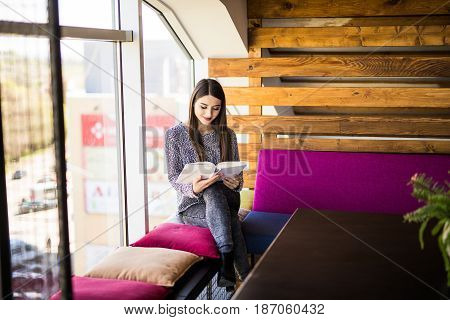 Woman Read Book Near Window In Cafe Shop