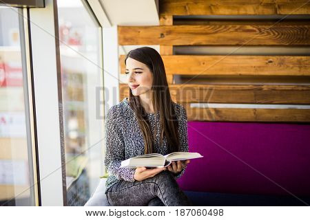 Woman Studying And Looking Through The Window
