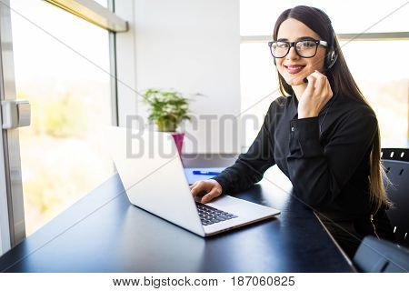 Female Customer Support Operator With Headset And Smiling In Office