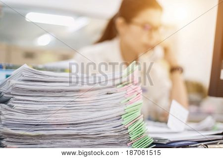 Document work is stacked on many tables. To wait for the sheratonWith a blurred image of a woman sitting at work.