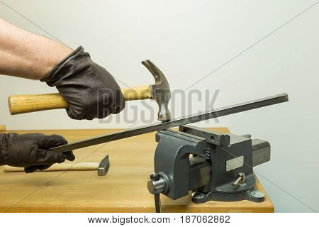 Caucasian Hands In Brown Leather Gloves Hammering A Piece Of Steel Iron With A Hammer Hold By A Vise