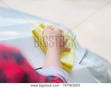 Hand with yellow microfiber cloth cleaning white car.