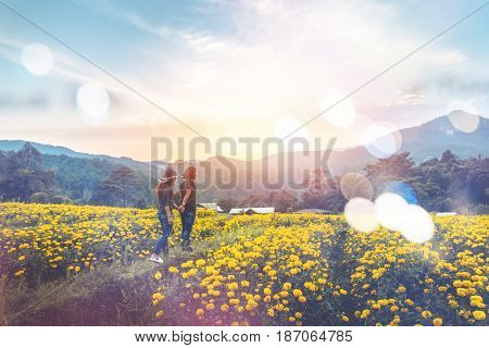 Couple of men and women walking in a field of yellow flowers. Evening sun