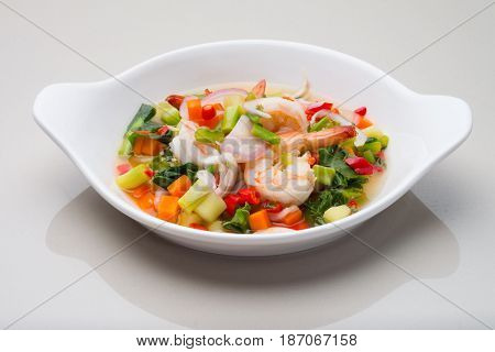 SPICY VEGETABLE SALAD WITH SHRIMPS, WHITE PLATE ON TABLE