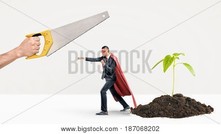 A tiny businessman in a red cape fighting off a giant hand with a saw while behind him a new plant grows. Protecting startups. New business. Business creation troubles.