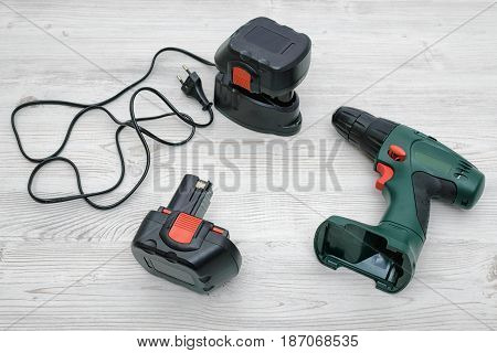 A green cordless drill, a spare battery and a charger on wooden table background. Repair and renovation. Electrical equipment. Tools of trade.