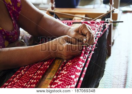 Old asia women demonstrate to procedure of making Thai Silk weaving in small weaving mill