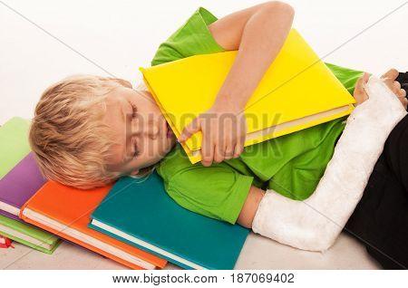 A boy with a broken arm had fallen asleep with a book