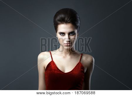 Beautiful woman with evening make-up and updo. Fashion photo. Girl wearing red dress ower dark background. Studio shoot.