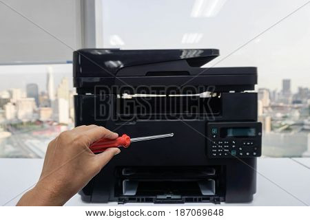 people left hand hold red screwdrivers for repair and maintenance office printer