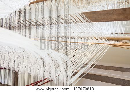 Yarn background old weaving Loom and thread of yarn. A traditional hand-weaving loom being used to make cloth at home.Background surface blurred.