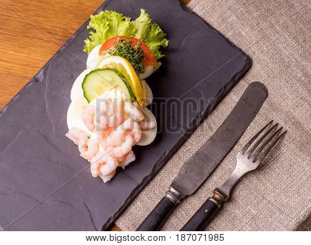 Danish specialties and national dishes high-quality open sandwich. Boiled Egg Shrimps mayo cucumber and lemon served on a plate and ready for eating