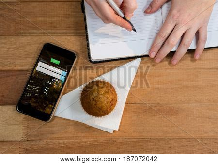 Digital composite of desk with phone, muffin and hands with agenda.