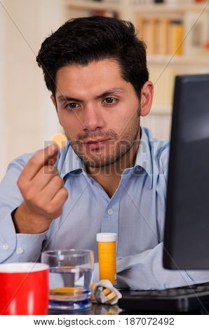 Handsome man holding a pill effervescent tablet in his hand in a office.