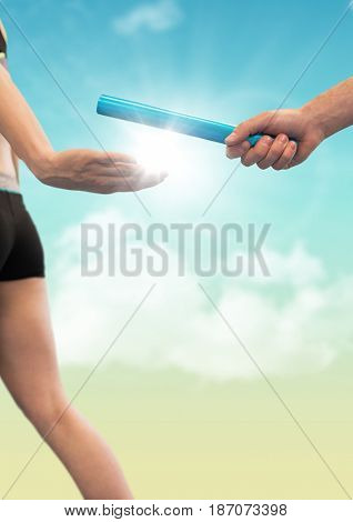 Digital composite of Runner and hand with blue baton against blue and yellow sky with flare