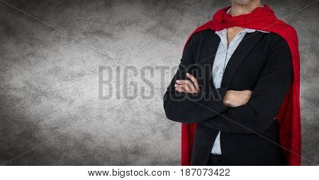 Digital composite of Business woman superhero mid section with arms folded against grey background and grunge overlay