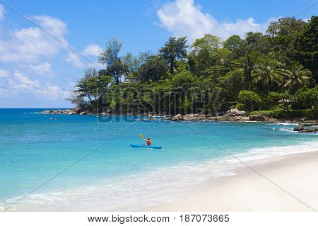 Tropical beach scenery at Andaman sea in Phuket Thailand. Exotic sea view with person kayaking at tropical summer paradise beach of Phuket island with sunny sky and clouds on horizon