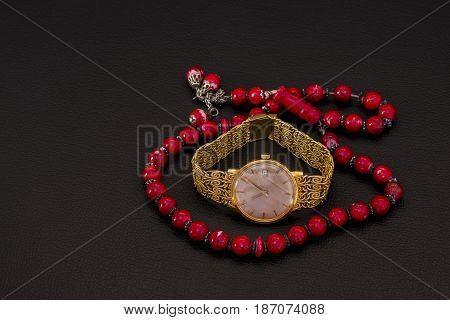string of beads for keeping count of prayers with a gold watch in the middle