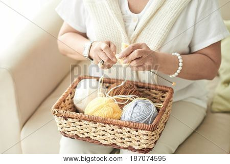 Hands of woman knitting a scarf at home