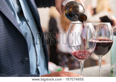 Man pours Red Wine In The Glass