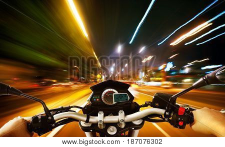Biker driving a motorcycle rides along the city street night scene . First person angle view .