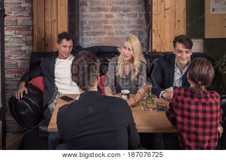 small group of people talking sitting sofa coffee shop table