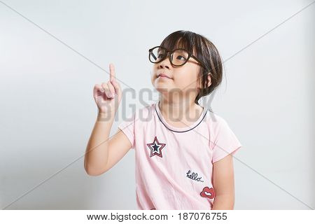 Little young cute asian girl fingers pointing up .