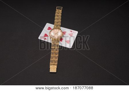 The nine of hearts underneath a gold hand watch
