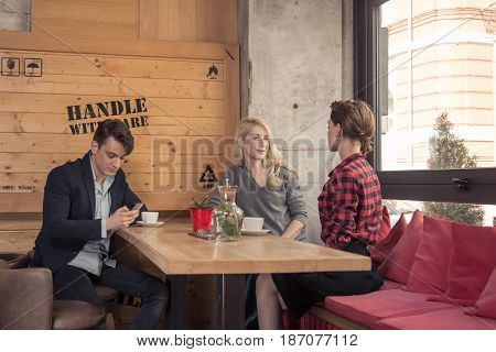 small group of people three people two women talking man using smartphone coffee shop indoors table coffee window