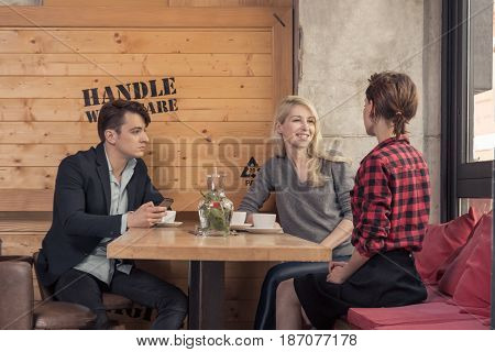 three people walking small group of people sitting in coffee shop indoors table man women table coffee