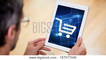 Digital composite of Man looking at shopping cart icon on digital tablet screen