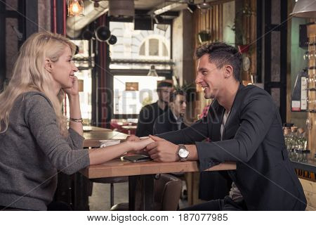 two small groups of people smiling happy couple holding hands coffee shop indoors