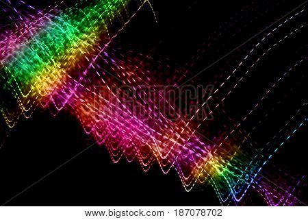 Abstract light painting of streaks of dotted lights in rainbow colors on black