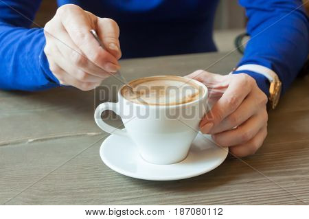hands of the girl stirring coffee behind a little table in cafe