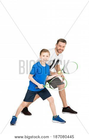 Side View Of Active Father And Son With Tennis Racquets Isolated On White