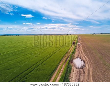 Tractor on country road through wheat field aerial view from drone pov