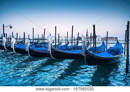 Venice gondolas or gondole on a blue sunset twilight and San Giorgio Maggiore church landmark on background. Italy Europe.