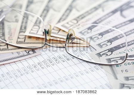 Closeup of spectacles and dollar banknotes on paper background with digits