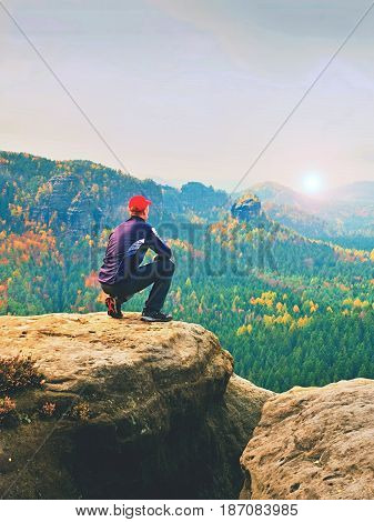 Moment Of Loneliness. Man In Black Enjoy Marvelous View. Hiker Sit On The Peak Of Rock