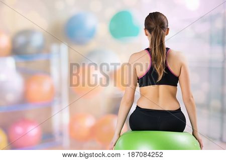 Digital composite of Rear view of woman sitting on fitness ball at gym