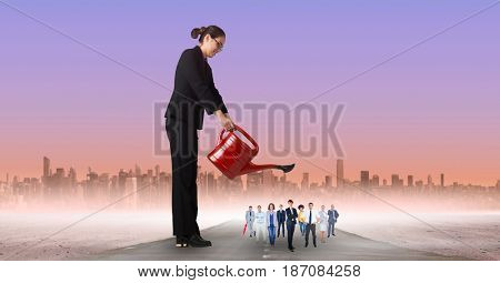 Digital composite of Businesswoman watering employees