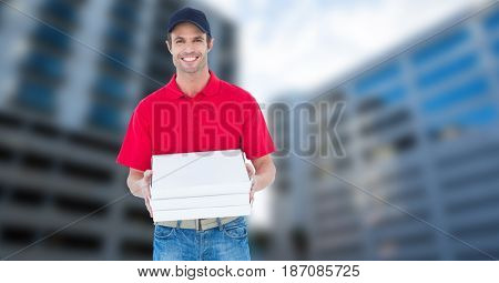 Digital composite of Portrait of smiling pizza delivery man holding pizza box against buildings