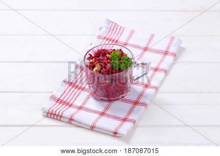 cup of fresh beetroot spread with walnuts on checkered dishtowel
