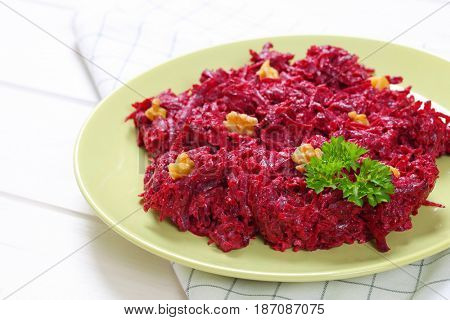 plate of fresh beetroot spread with walnuts on checkered dishtowel - close up
